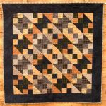 Brown, black and grey small quilt using the Northerrn Lights block