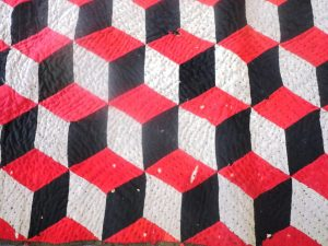 Antique quilt made of Red, grey and black tessellating diamonds