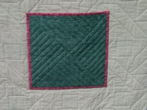 Green pocket stitched onto the quilt back