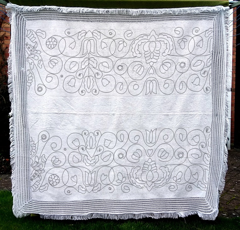 Black lines of pattern are drawn over the white-on-white quilt