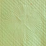 Fourfold fan motif hand-quilted on green Welsh quilt