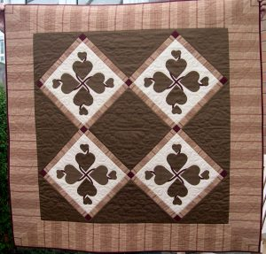 Brown and cream quilt with appliqued hearts