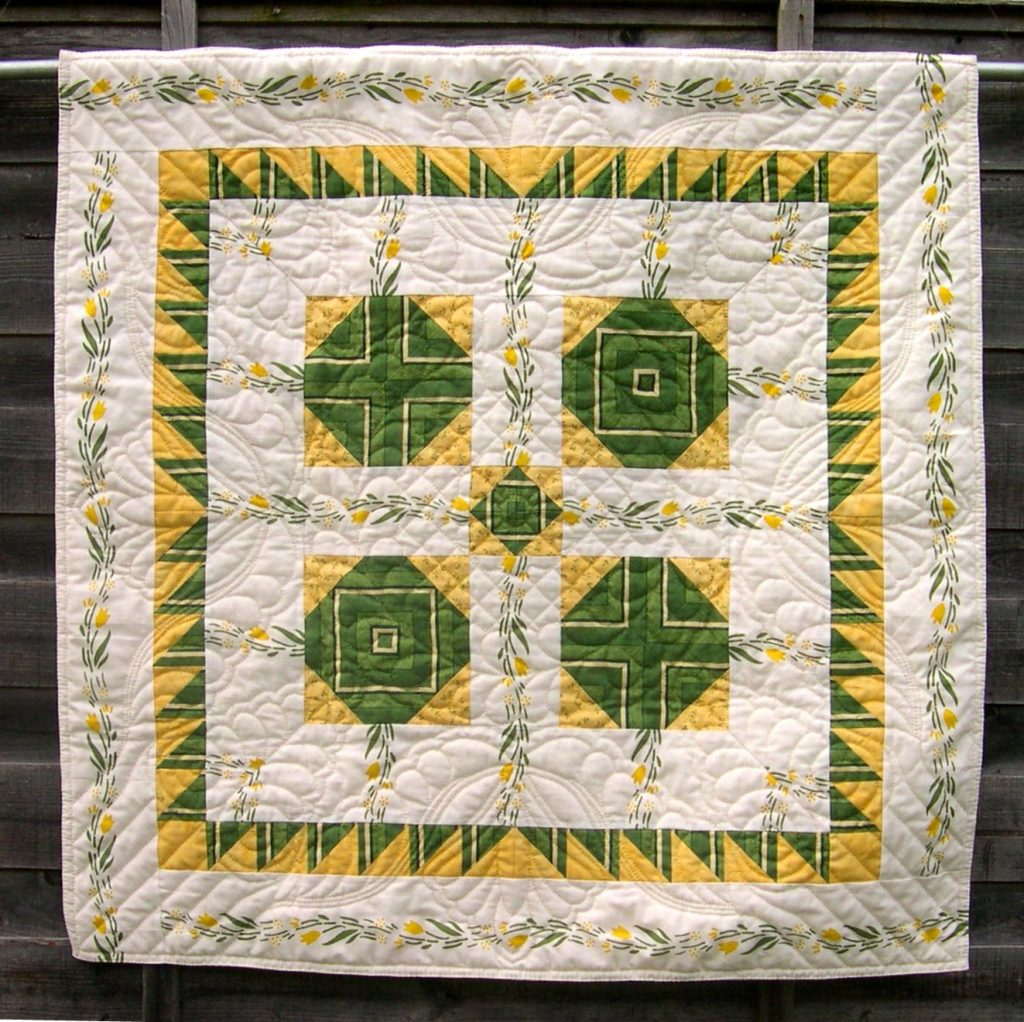 White quilt with green and yellow patchwork and hand quilting