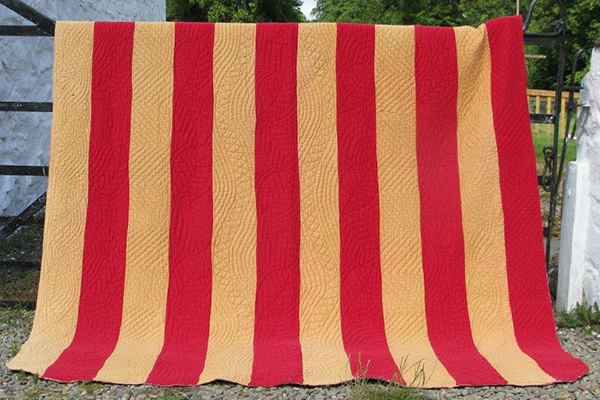 Red and sand strippy quilt