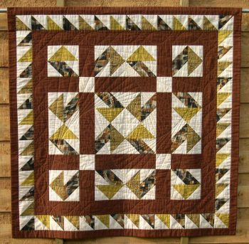 Brown aand ye;llow patchwork quilt in Jack-in-a-Box design