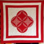 Red and white quilt with striped fabric