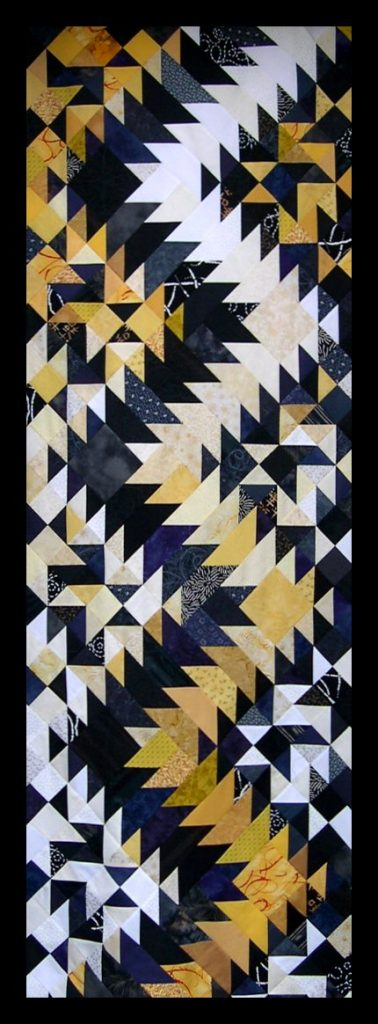 Patchwork in the shape of a zig-zag lightning flash made from many yellow, black and white triangles