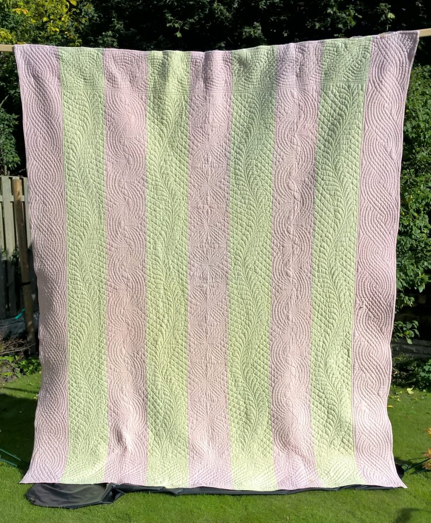 Quilt with pink and white alternating strips