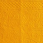 Bright yellow quilt with paisey border