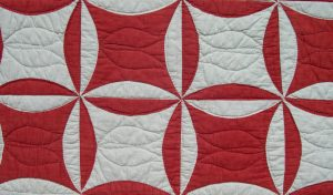 Antique quilt with red and white circular motifs
