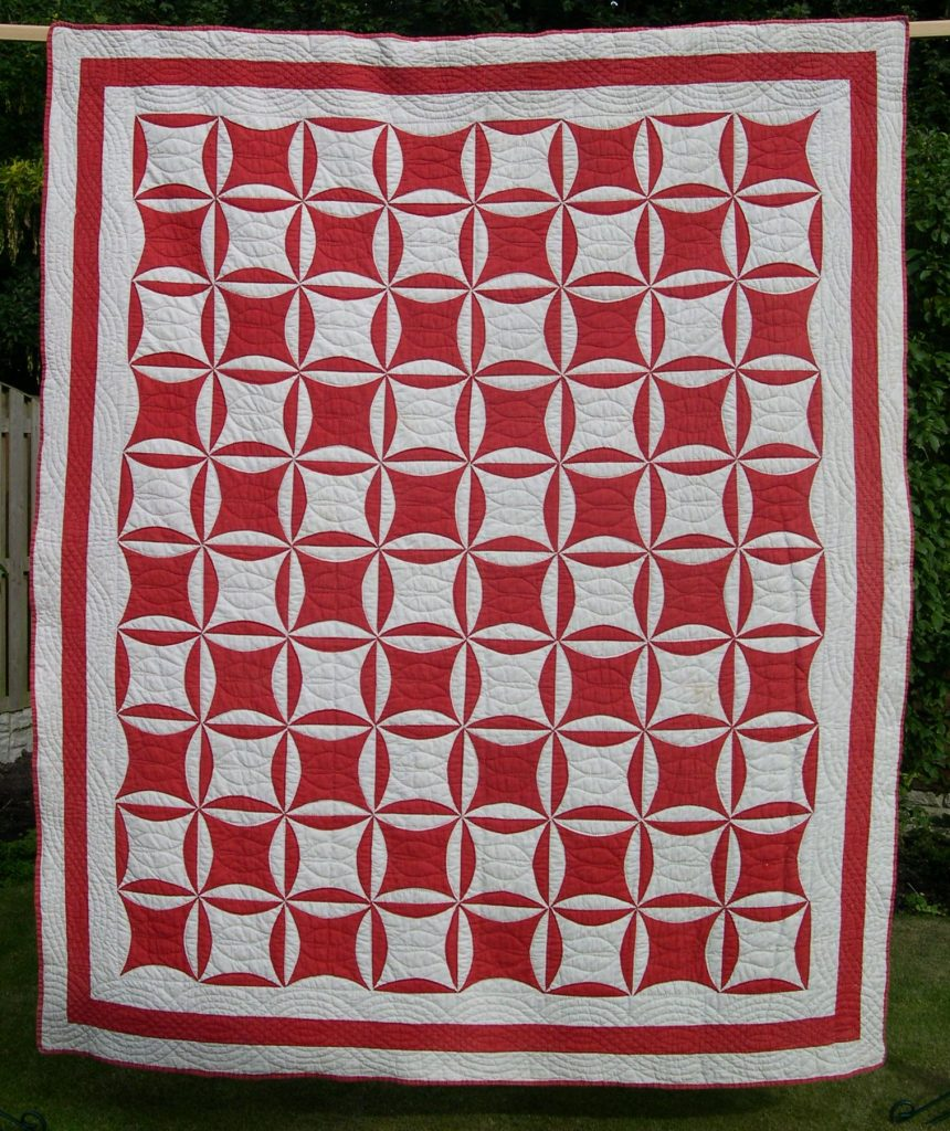 Red and white quilt with circular motifs