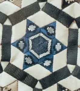 Antique patchwork close-up showing a blue and white star made from diamonds