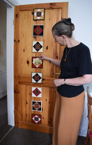 Carolyn standing next to door with red, black and cream square units of patchwork holding cards