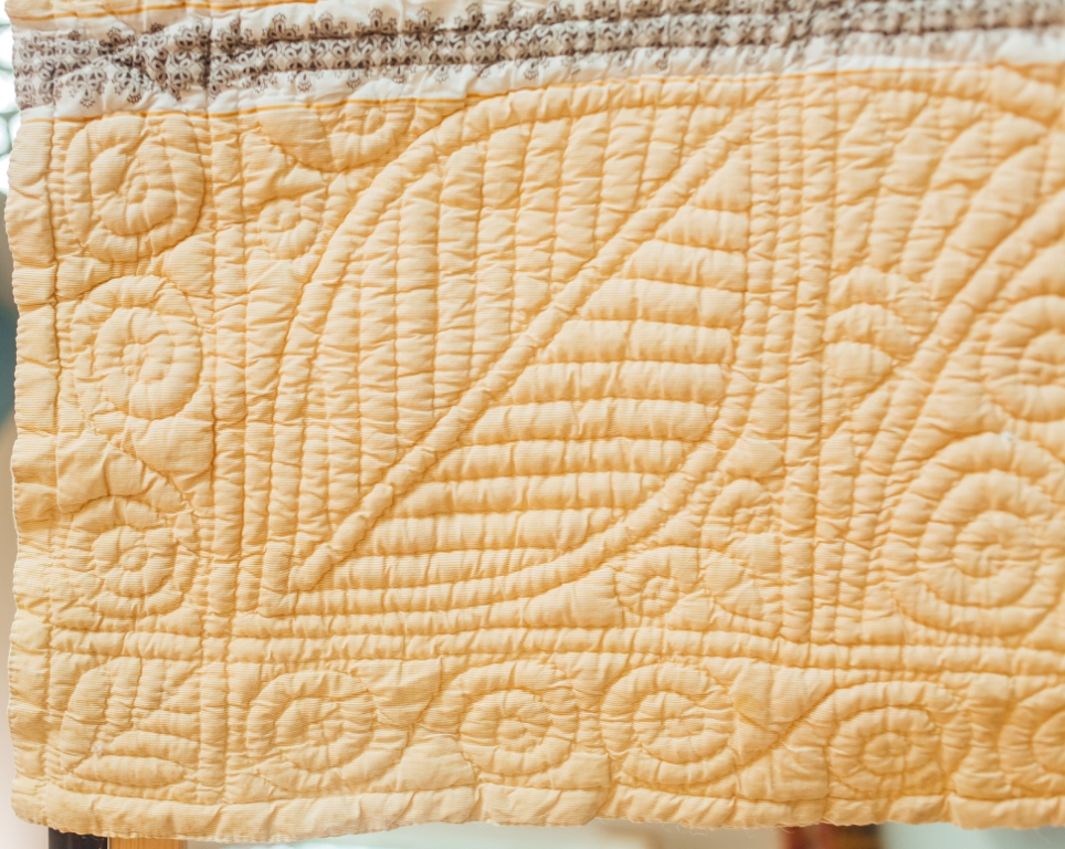 Large and small beech leaves form the corner square on hand quilted border
