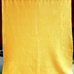 Large yellow hand-stitched quilt