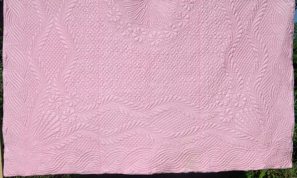 Pale pink quilt with feather bellows quilting design