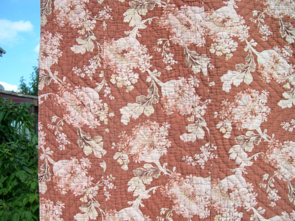 Narrow strip of floral fabric stitched onto the edge of the quilt back