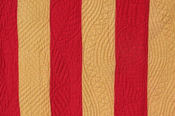 Red and pale gold strips of fabric.