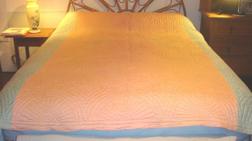 Salmon pink and blue quilt on bed