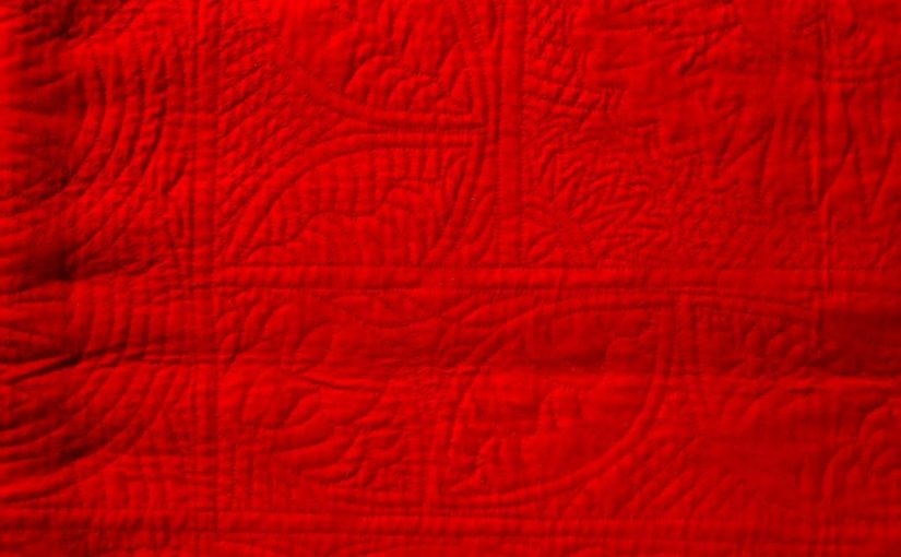 Red woolen quilt with hand-stitched quilting designs.