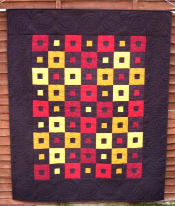 A simple but striking lap quilt in red, yellow and black