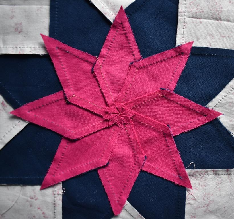 Pink star pieces with seam allowance maniplulated into a spiral