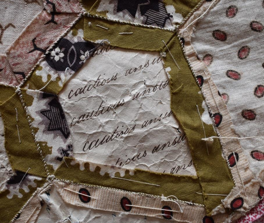 "The hand-written phrase ""cautious answer"" is repeated several times on the paper used in this quilt top."
