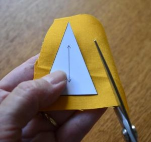 Yellow fabric being cut out using card triangle template