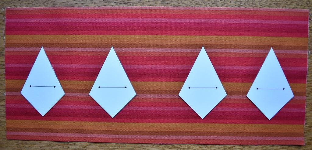 Four card templates lined up on striped fabric placed horizontally