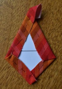 Red stripy fabric tacked over kite-shaped card