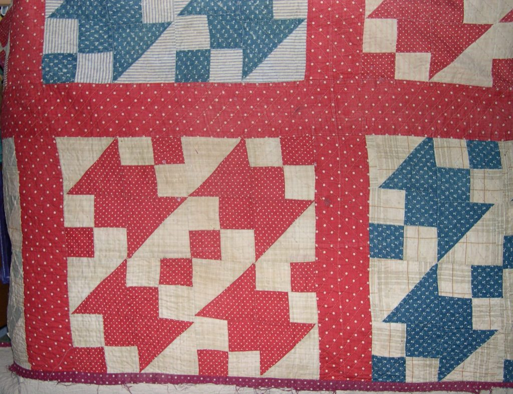 Four red and cream patchwork blocks arranged next to each other