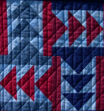 Vertical and diagonal lines of quilting over patchwork