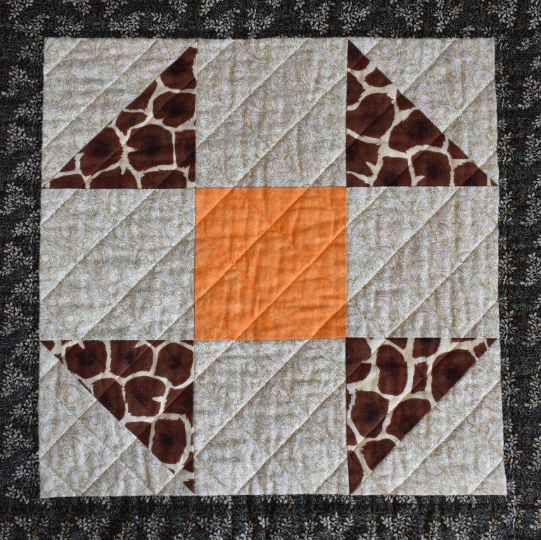 Brown and orange simple patchwork block with diagonal quilted grid.