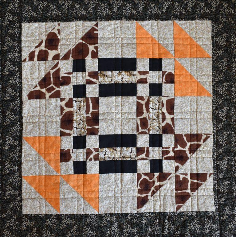 Brown and orange patchwork block with quilted double lined grid