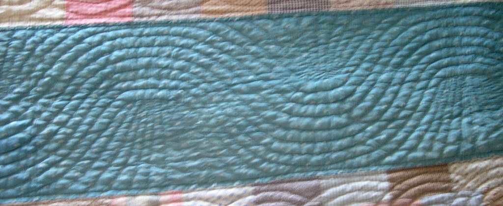 Large waving lines of stitching flow along the blue fabric strip, with a spray infill