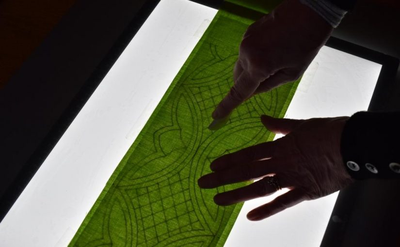 Design being traced onto green fabric