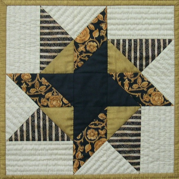 Black, gold and cream star block, with simple lines of quilting in cream background.