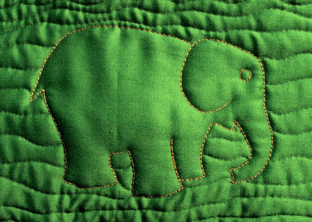 Quilted elephant design on green background