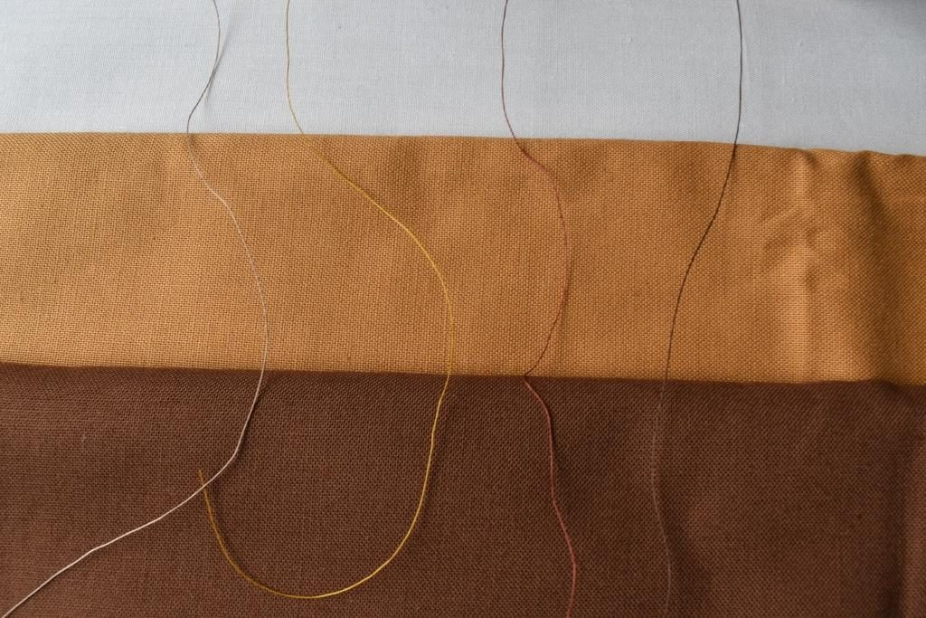 Four threads (grey, yellow, rust and dark brown) spread across three fabrics (white, sand, brown)