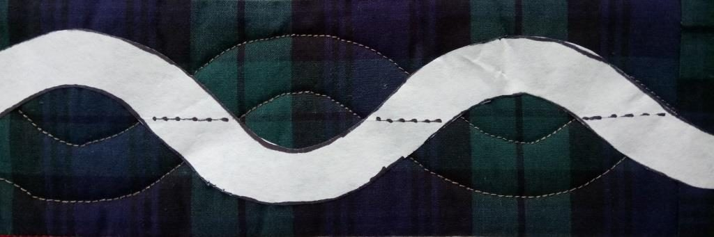 Paper waving line forming one strand of a quilted cable design