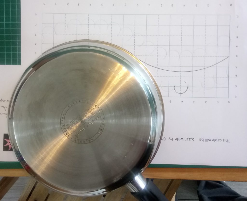 Frying pan laid upside-down, being used to draw curve