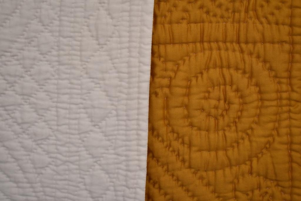 White quilting has small stitches and a flat effect; deep yellow quilt has larger stitches, but the design is more prominent