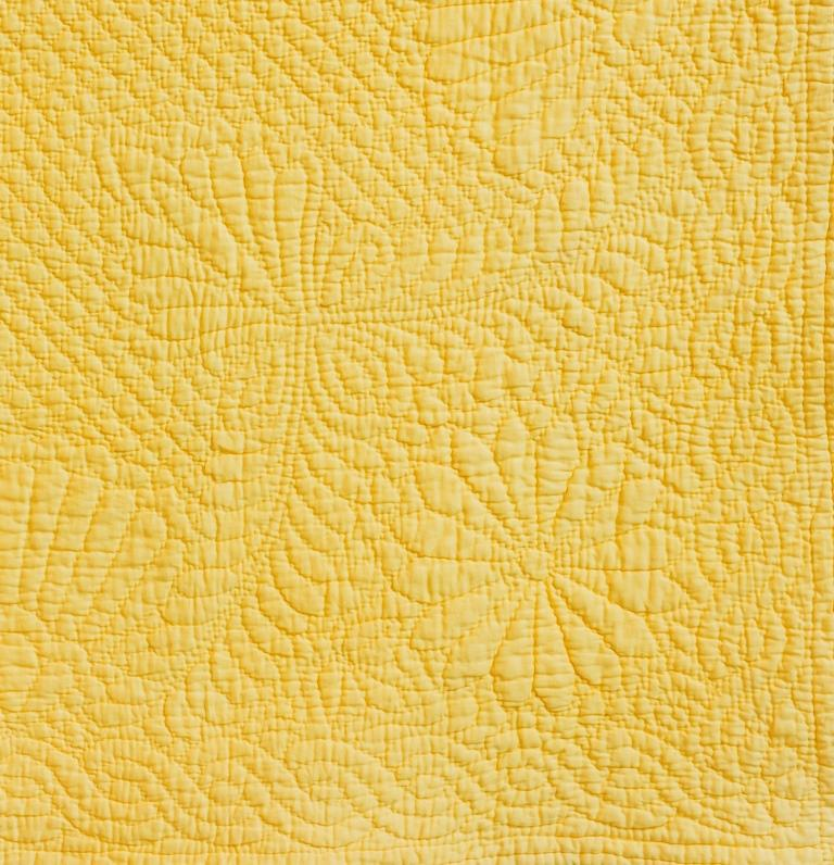 Flower and feather motifs quilted onto yellow cloth