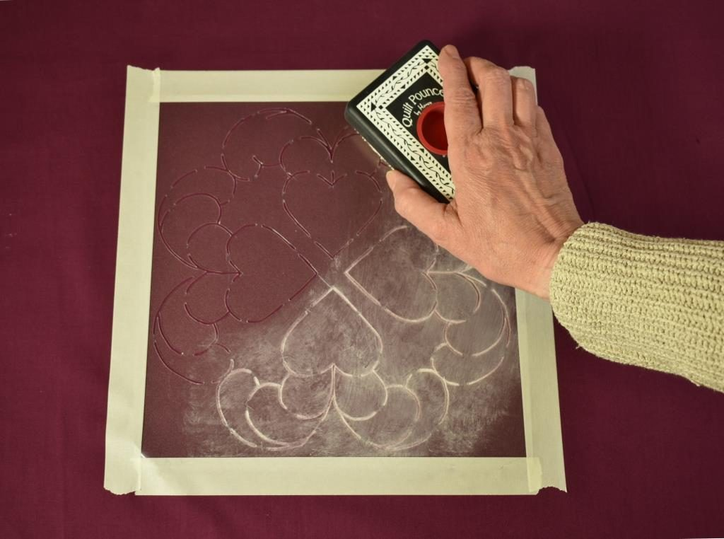 "White chalk used in a ""pounce pad"" to mark a stenciled design on purple fabric."