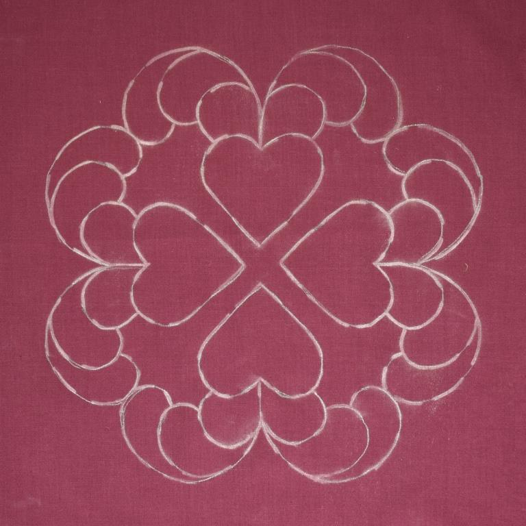 White chalky lines show the design of hearts and feathers on purple fabric.