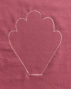White outline of cowslip leaf on purple fabric