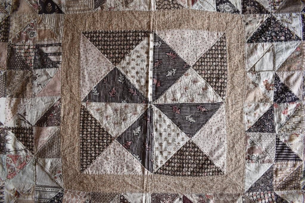Four quarter-square triangle units of patchwork in brown and cream