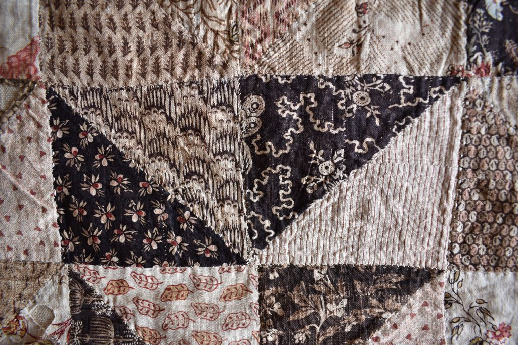 Small pieces of dark printed fabrics have been stitched together to make some of the triangles in this patchwork.
