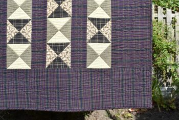 Running feather border o purple fabric around simple quarter square triangle blocks