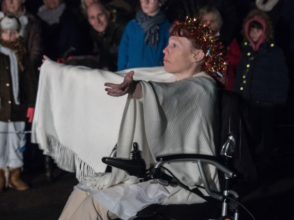 Woman dressed as angel, in wheelchair with outstretched arms.
